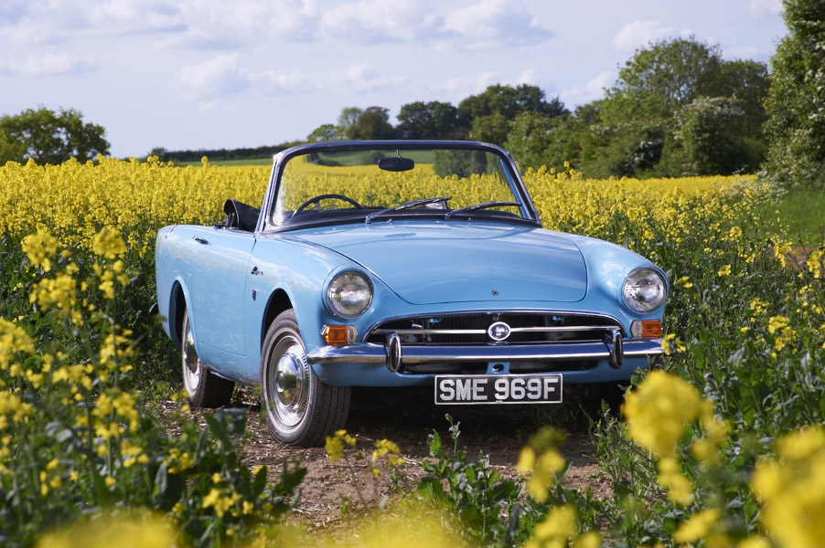1967 Sunbeam Alpine in Mediterranean Blue in middle of rapeseed oil field