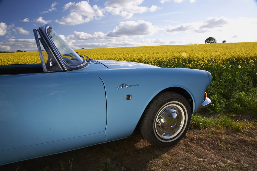 1967 Sunbeam Alpine in Mediterranean Blue in rapeseed oil field