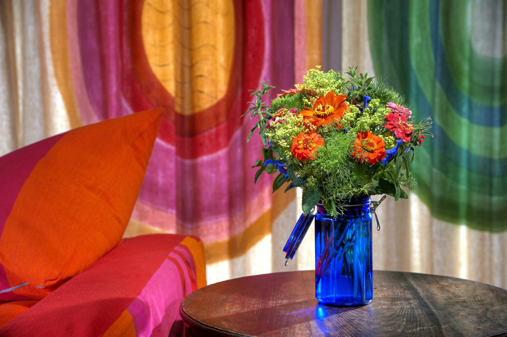 Vibrant flowers in blue vase in modern sitting room at Chaucer Barn