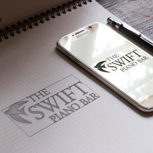 The Swift Piano Bar Logo in pencil and on a smartPhone